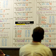 LAS VEGAS, NV - JANUARY 15:  A bettor contemplates the plethora of betting options before submitting a wager in the sports book inside the Green Valley Ranch Resort and Spa in Las Vegas on January 15, 2005. Sports Illustrated rated the sports book, complete with oversize, leather chairs, as one of the top places in the country to watch sports. (Photo by Todd Bigelow/Aurora)
