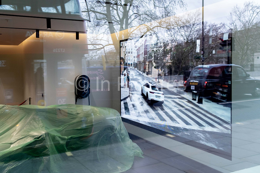 Protected against the dust during the closure of non-essential businesses during the Coronavirus pandemic, luxury Porsche cars are under cover in the companys Piccadilly showroom in Londons West End, on 4th March 2021, in London, England.