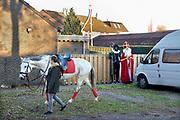 Nederland, Milsbeek,18-11-2018Sinterklaas en zwarte Piet bereiden zich voor op hun intocht. Hier verstoppen ze zich achter een auto om niet door de voorbijlopende kinderen gezien te worden..het paard loopt alvast warm.Foto: Flip Franssen