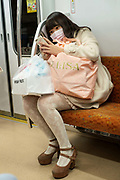 Young woman on her smart phone with her shopping on the subway. Tokyo, Japan
