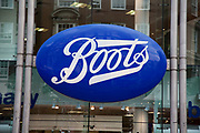 Sign for a Boots chemist store on Oxford Street in Central London. This is a busy shopping area full of all the main high street chain stores.