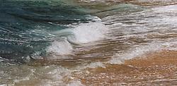 Waves wash ashore onto the beach of Wainiha Bay near the Hanalei Colony Resort on the north shore of the island of Kauai in Hawaii.