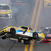 Regan Smith (7) flips in his car after being struck by Daniel Suarez (18) on the front stretch during the Alert Today Florida 300 XFinity Series race at Daytona International Speedway on Saturday, February 21, 2015 in Daytona Beach, Florida.  (AP Photo/Alex Menendez)