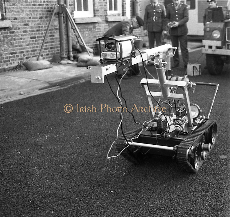 Bomb Disposal Robot.   (J97)..1975..29.12.1975..12.29.1975..29th December 1975..At Clancy Barracks,Dublin the Irish army put on display their newly aquired Bomb Disposal Robot. It would be invaluable in inspecting suspect buildings or vehicles. The series of pictures shows the army demonstration of the equipment..Image shows the vehicle heading on its way to the suspect car.