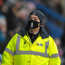 TELFORD COPYRIGHT MIKE SHERIDAN A steward wears a face mask during the Conference North fixture between AFC Telford United and Chester FC at New Bucks Head on Saturday, December 26, 2020.<br /> <br /> The fixture was the first occasion since March where fans had been allowed to attend at the New Bucks Head Stadium.<br /> <br /> Picture credit: Mike Sheridan/Ultrapress<br /> <br /> MS2021-051