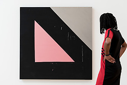 "© Licensed to London News Pictures. 07/06/2016. London, UK.   A staff member views ""Orbit"", by the American artist Mary Heilmann, which is previewed ahead of her first major UK exhibition, ""Looking at Pictures"", at the Whitechapel Gallery.  The exhibition spans the artist's five decade career, from her early geometric paintings made in the 1970s to her recent shaped canvases in day-glo colours.  The show features approximately 45 paintings as well as a selection of ceramics, chairs and works on paper, many of which have never been exhibited.  Photo credit : Stephen Chung/LNP"