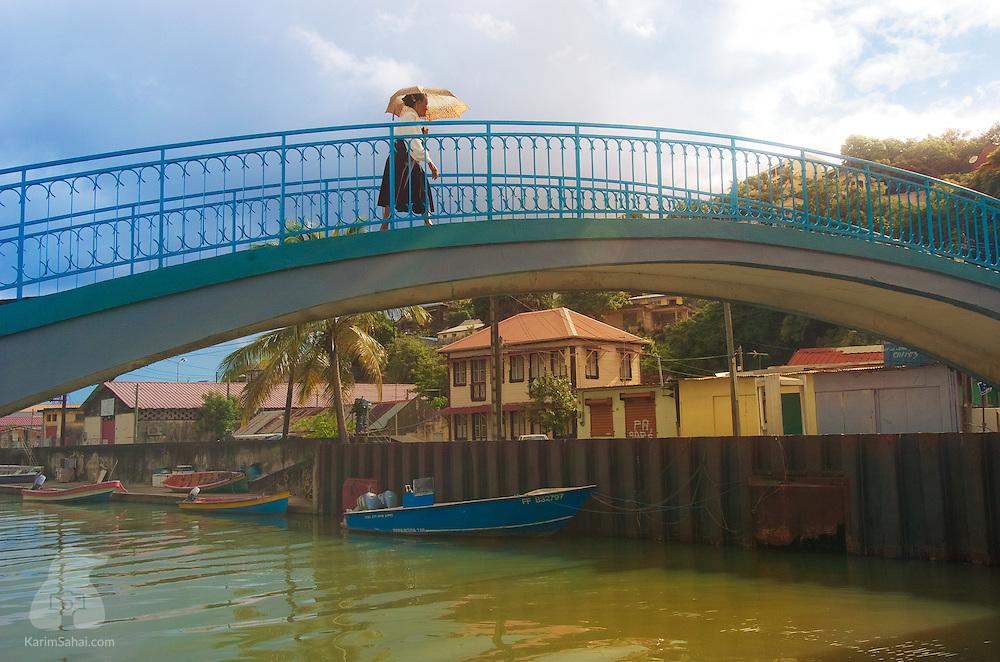 A woman walks on a bridge crossing Canal Levassor, Fort-de-France, Martinique.