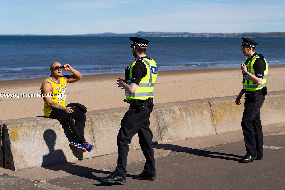 Portobello, Edinburgh. Scotland, UK. 11 April, 2020. Easter bank holiday weekend Saturday afternoon in very warm sunny weather the public are outdoors exercising and walking on Portobello beach. The popular beach and promenade was very quiet and people were mostly exercising proper social distancing. Pictured; Police patrolling the promenade stop to talk to a man sitting on seawall. He was asked to move on.  Iain Masterton/Alamy Live News