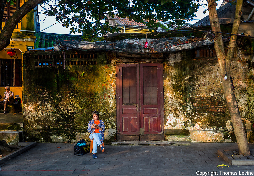 Woman sits in front of old ancient town building.