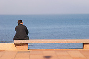 A man in black sitting on a red stone bench faxing the river sea looking right in profile, on the riverside seaside walk along the river Rio de la Plata Ramblas Sur, Gran Bretagna and Republica Argentina Montevideo, Uruguay, South America