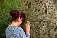 woman leaning against an old beech tree in the nature reserve de Manteling near Oostkapelle on the peninsula Walcheren, Zeeland, Netherlands.<br /> <br /> Frau steht an einer alten Buche im Naturschutzgebiet de Manteling bei Oostkapelle auf Walcheren, Zeeland, Niederlande.