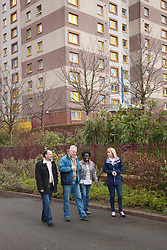 Tenants and housing officer in front of flats.