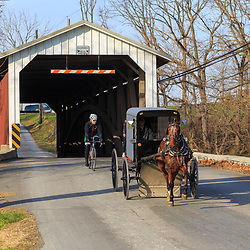 Paradise, PA, USA - December 6, 2015: A cyclist follows an Amish buggy exiting a covered bridge in Lancaster County, Pennsylvania.