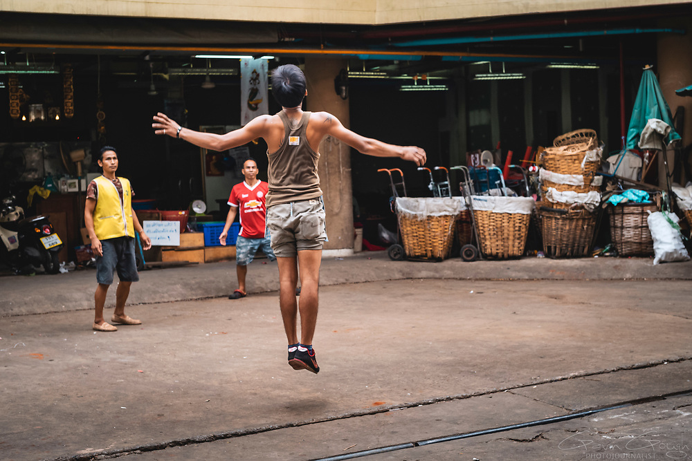 A man playing Sepak Takraw appears to be levitating whilst jumping in the air to reach a ball, Pak Khlong Talat, Bangkok, Thailand