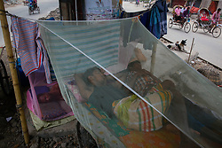 June 21, 2017 - Dhaka, Bangladesh - Bangladeshi three wheeler puller shelter in mosquito's net during their sleep to safe himself from mosquito beside the street at Dhaka on June 21, 2017.As Chikungunya and dengue viruses transmitted by the same mosquitoes sometimes it is difficult to distinguish chikungunya and dengue based on clinical findings alone. Joint pain feature is more prominent in Chikungunya fever. Chikungunya fever is a new terror in Dhaka city. It's spreading very fast in Dhaka. (Credit Image: © Mehedi Hasan/NurPhoto via ZUMA Press)
