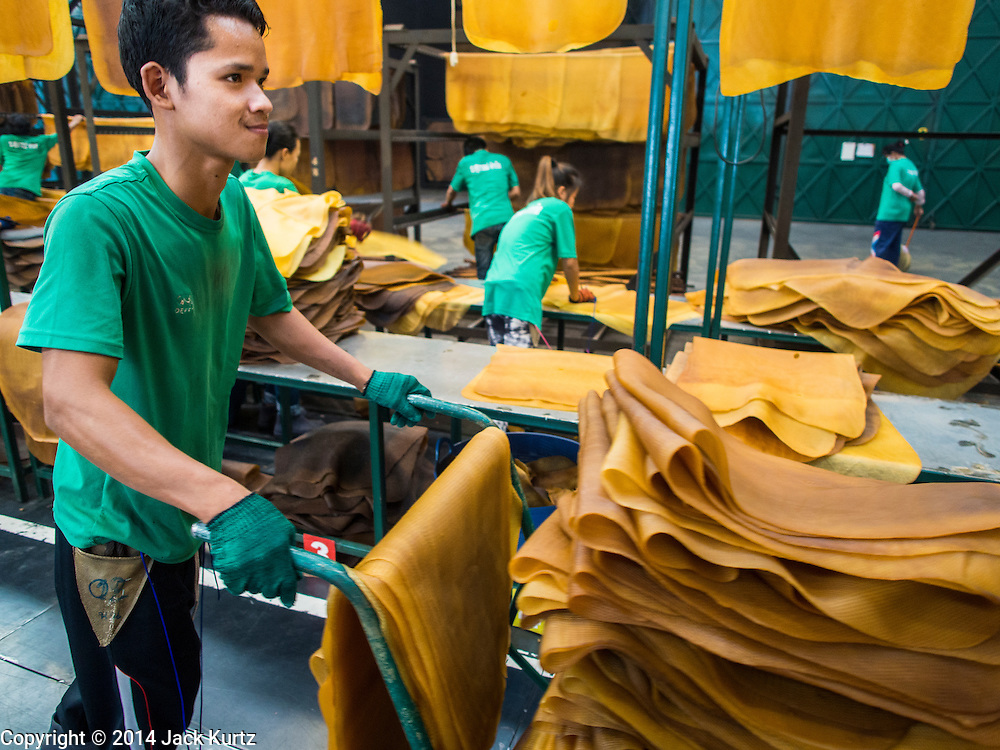 """15 DECEMBER 2014 - KLAENG, RAYONG, THAILAND: A worker pushes a cart of dried rubber to a packing station at Supark, a rubber processing plant in Klaeng, Thailand. Thailand is the second leading rubber exporter in the world. In the last two years, the price paid to rubber farmers has plunged from approximately 190 Baht per kilo (about $6.10 US) to 45 Baht per kilo (about $1.20 US). It costs about 65 Baht per kilo to produce rubber ($2.05 US). Prices have plunged 5 percent since September, when rubber was about 52Baht per kilo. Some rubber farmers have taken jobs in the construction trade or in Bangkok to provide for their families during the slump. The Thai government recently announced a """"Rubber Fund"""" to assist small farm owners but said prices won't rebound until production is cut and world demand for rubber picks up.        PHOTO BY JACK KURTZ"""