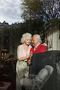 Wolf C Hartwig aged 91, producer of epic films and soft-porn features, with his fourth wife, and actress, Veronique Vendell in their apartment on Avenue de Foch, Paris. Wolf Hartwig was awarded a Bambi Award from German Cinema for his film 'The Iron Cross' which was directed by Sam Peckinpah starring James Coburn with Veronique Vendell. A producer working in exploitation genres, soft porn, sex, lurid, violent and sensational features. Other films he produced include 'Horrors from Spider Island'. 'Lady Hamilton' and 'Virgin of the Seven Seas'.//Wolf Hartwig and his wife Veronique Vendell viewed through window from their front garden, avenue Foch in reflection