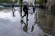 A wet Londoner walks along the paved area outside the National Gallery during seasonal Spring rainfall, on 24th May 2021, in London, England.