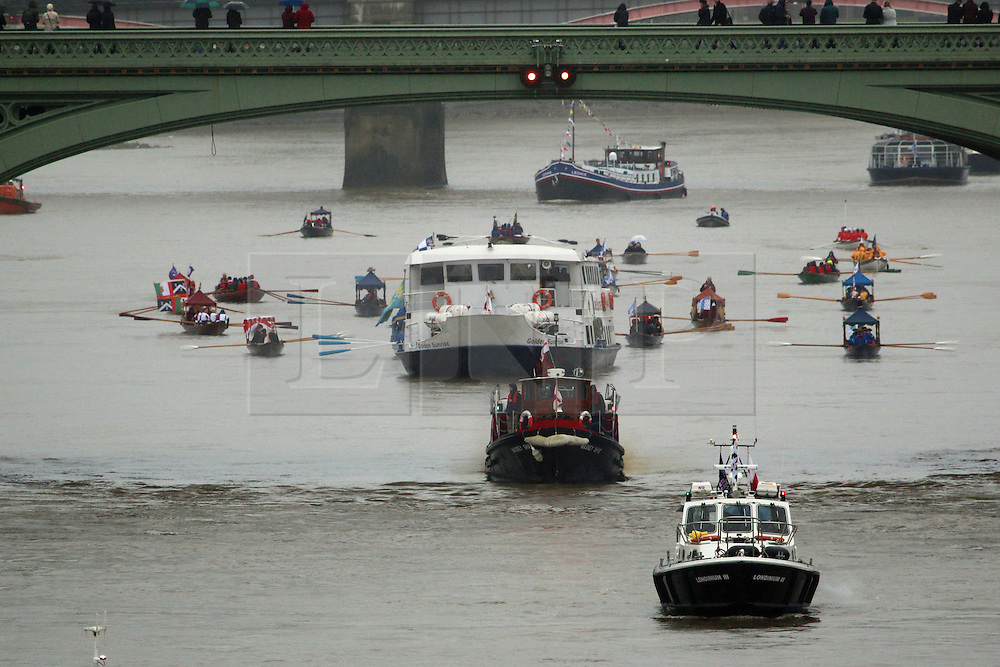 © Licensed to London News Pictures. 14/11/2015.  The brand new Lord Mayor of London has travelled down the Thames this morning as part of a 40 boat flotilla. The new Lord Mayor Jeffrey Evans was due to be on board the Queen's row barge Gloriana but due to wet weather conditions he instead travelled on the passenger boat Golden Sunrise. Tower Bridge opened in salute and the new Lord Mayor came ashore at HMS President before preparing for the rest of the Lord Mayor's Show today in the City of London. This year's Lord Mayor's Show is the 800th time the event has taken place. The classic fireboat Massey Shaw joined the flotilla and pumped water into the sky. Two military ribs also accompanied the procession in a sign of increased security. Credit: Rob Powell/LNP