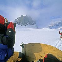 BAFFIN ISLAND, Nunavut, Canada.  Expedition snowmobiles up Stewart Valley towards Sail Peaks (bkg).