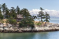 Sculpted sandstone cliffs on the edge of Sturdies Bay on Galiano Island.  Photographed from the BC Ferry Salish Eagle in Sturdies Bay, Galiano Island, British Columbia, Canada.