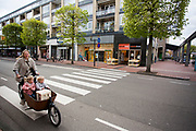 In Zeist rijdt een vrouw met kinderen en boodschappen door het centrum.<br /> <br /> In Zeist a woman cycles with two children and groceries on a cargo bike in the city center.