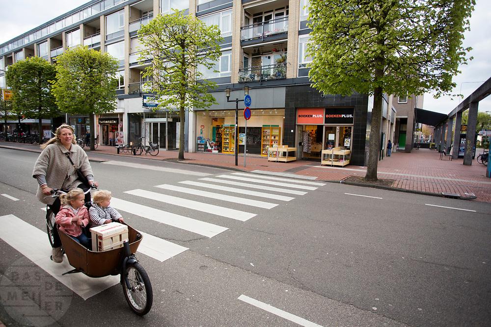 In Zeist rijdt een vrouw met kinderen en boodschappen door het centrum.<br /> <br /> In Zeist a woman cycles with two children and groceries on a cargo bike in the city center.