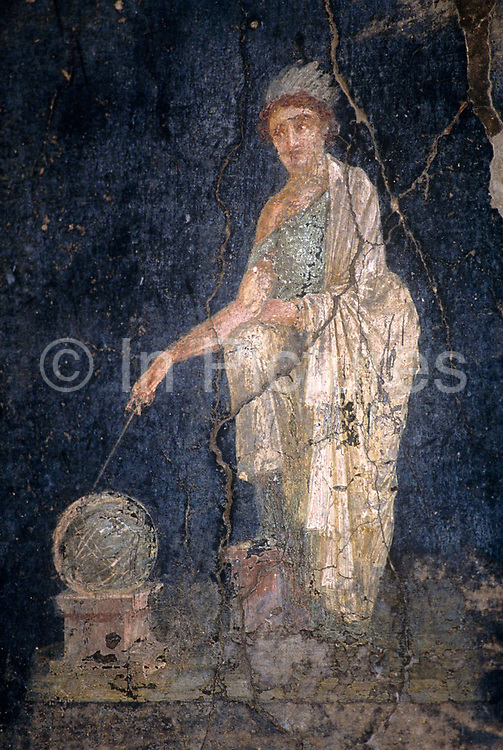 In the peristyle of the House of the Vettii in Pompeii is a fresco  where an ancient painted mural to the Greek Goddess Urania was unearthed from volcanic ash after 2,000 years. In Greek mythology, Urania which stems from the Greek word for 'heavenly' or 'of heaven', was the muse of astronomy. Some accounts list her as the mother of the musician Linus, usually depicted as having a globe in her left hand, she can foretell the future by the arrangement of the stars and is often associated with Universal Love and the Holy Spirit. Those who are most concerned with philosophy and the heavens are dearest to her. Painted before the catastrophic eruption of Versuvius in AD79, the frescoes have been uncovered from metre-layers of ash and pumice but are now fading from moisture and cracked plaster.