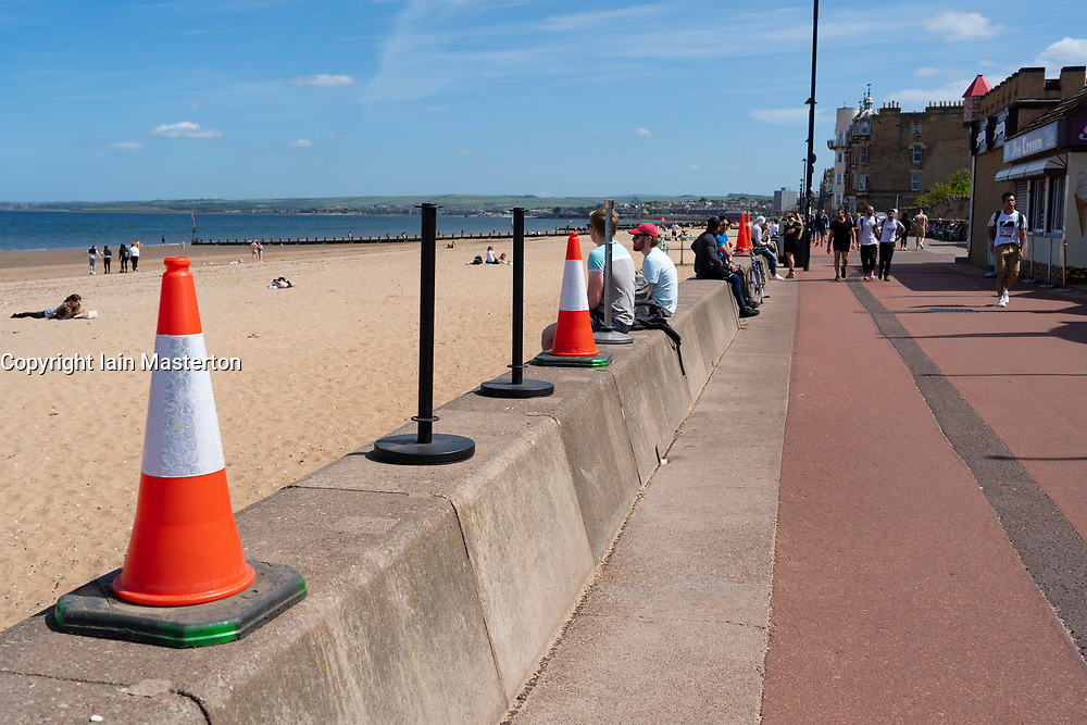 Portobello, Scotland, UK. 26 May 2020. Portobello beach and promenade were relatively quiet despite sunny warm weather. Police patrols on foot were low key and officers were not asking many members of the public to move on. Pictured; promenade cafe placed traffic cones on seawall to stop public sitting down. Iain Masterton/Alamy Live News