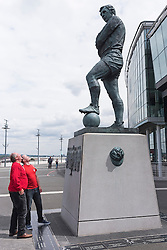 © Licensed to London News Pictures. 30/07/2016. Fans pose for photos next to the bronze statue of England footballer BOBBY MOORE outside Wembley Stadium on the 50th anniversary of England beating Germany in the World Cup finals on 30th July 1966.  London, UK. Photo credit: Ray Tang/LNP