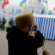 December 19, 2013 - Kiev, Ukraine: A pro-EU protestor takes photos of other demonstrators at Independence Square.<br /> On the night of 21 November 2013, a wave of demonstrations and civil unrest began in Ukraine, when spontaneous protests erupted in the capital of Kiev as a response to the government's suspension of the preparations for signing an association and free trade agreement with the European Union. Anti-government protesters occupied Independence Square, also known as Maidan, demanding the resignation of President Viktor Yanukovych and accusing him of refusing the planned trade and political pact with the EU in favor of closer ties with Russia.<br /> After a days of demonstrations, an increasing number of people joined the protests. As a responses to a police crackdown on November 30, half a million people took the square. The protests are ongoing despite a heavy police presence in the city, regular sub-zero temperatures, and snow. (Paulo Nunes dos Santos/Polaris)