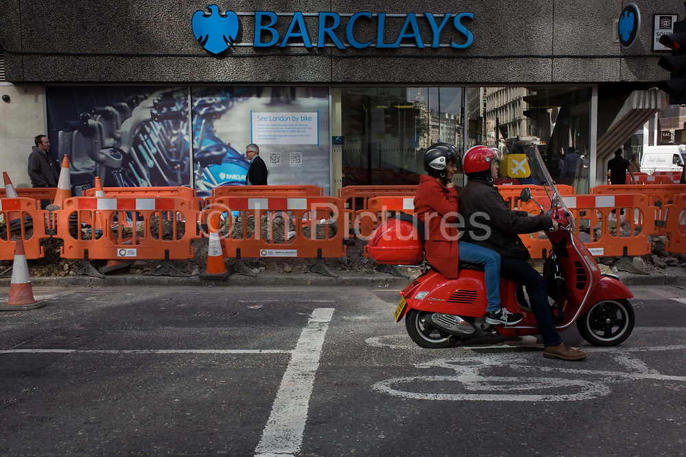 Exterior of the Barclays Bank branch and outside roadworks in Moorgate, City of London. A scooter rider and his passenger stop at a red light in an area designated for cyclists but they are stationary before continuing their journey. A branch of Barlcays Bank is in the background with disruptive roadworks fencing by mound of soil. Barlays sponsor the the so-called Boris Bikes that can be rented across the capital and an ad for that service can be seen on the bank's wall.