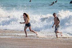 A young couple running on Fistral Beach in Newquay, Cornwall.