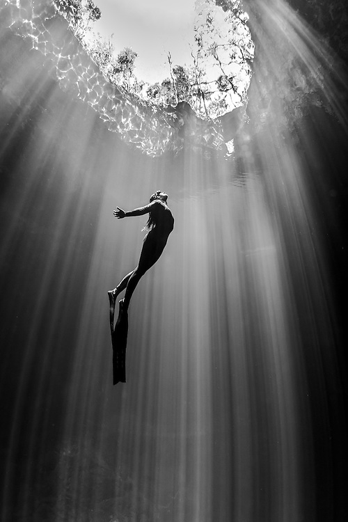 Mexico, Quintana Roo. A freediver champion surfaces between the sunrays at cenote The Pit.