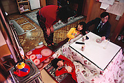 Sayo Ukita asks her daughter Mio what she would like for breakfast in the kitchen/dining room. Maya continues her morning wakeup at the table as their father Kazuo Ukita enjoys his morning cigarettes while watching television before leaving for work. The house is unheated. There is an electric heater under the table, covered by a quilted blanket. Japan. Published in Material World: A Global Family Portrait, page 50. The Ukita family lives in a 1421 square foot wooden frame house in a suburb northwest of Tokyo called Kodaira City.