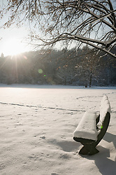 Snow-covered bench in winter landscape, Bavaria, Germany