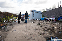 © London News Pictures. Calais, France. 15/01/16. Two Eritrean men, whose home is to be demolished, wheel their belongings away ina  shopping trolley.French authorities are to bulldoze a 100-metre 'buffer zone' between the camp and the adjacent motorway, which leads to the ferry port. Photo credit: Rob Pinney/LNP