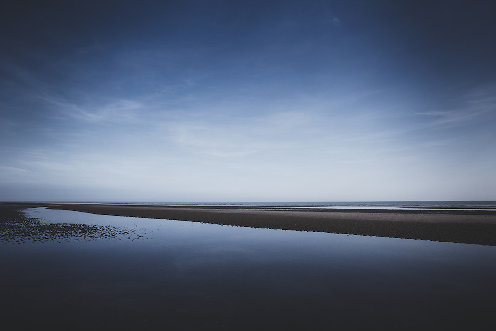 Blue sky over the beach and sea at Camber Sands, southeast England, UK.