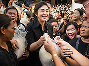 11 NOVEMBER 2016 - BANGKOK, THAILAND: YINGLUCK SHINAWATRA (center) sells a sack of rice to a man at a rice distribution sale in the Bangkok suburbs. Yingluck Shinawatra, the former Thai Prime Minister deposed in a coup in 2014, has started selling rice directly to Thai consumers. She buys the rice from farmers at market prices and then sells it to urban consumers at the price she paid. She said she's doing it to help out farmers, who are trying to deal with depressed prices. Yingluck is facing prosecution on corruption related charges going back to a rice price support scheme her government used to try to help farmers in 2011 and 2012. Even after the coup, she is still personally popular and hundreds of people showed up to see her at the rice distribution point at a mall in Samut Prakan province, in suburban Bangkok.   PHOTO BY JACK KURTZ