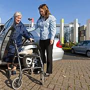 Foto: David Rozing  Etten Leur Jonge vrouw helpt oudere dame met uitstappen uit taxi, taxichauffeur, verveor op maat. Ouderen. , lopen met rollator, broze gezondheid, broos, broze, wankele tred. Bewegen., oud, oude, oude dag, oude knarren, oude van dagen, ouder worden, ouderdom, ouderdom komt met gebreken, oudere, ouderen, ouderenbus, ouderenbusje, ouderenvervoer, ouderenzorg, pensioen, pensioenen, pensioengerechtigde, pensioengerechtigden, pensioenleeftijd, pensioensysteem, pensioenuitkeringen, pensioenuitkeringstelsel, pensioenvermogens, pensionado, pensionado's, people, people and lifestyle, personen, persoon, polder, regiotaxi, retired, retirement, rollator, rolstoel, samen, samen leven, samen werkt beter, samenleven, samenleving, samenwerken, samenwerking, senioren, seniors, slecht ter been, sociale banden, sociale cohesie, sociale samenhang, speciaal vervoer, sterftecijfer, steun, steunen, steunen op, stokoud, stokoude, straatbeeld, taxi, taxibus, te been blijven, te voet, tezamen, together, transporteren, transportmiddel, transportmiddelen, uit de auto helpen, uitrusten, uitstappen uit auto, uitzicht, van a naar b gaan, vergankelijk, vergankelijke, vergankelijkheid, vergrijzen, vergrijzende samenleving, vergrijzing, vervoer op maat, vervoer ouderen, vervoermiddel, vervoersmiddel, vijftig plusser, vitaal, vitale, vitaliteit, voetganger, voetganger  voetgangers, voorjaar, vrijwilliger, vrijwilligerswerk, vrouw, vrouwen, wagentje, wandelstok, wankel, wankele tred, zelfstandig leven, zelfstandig zijn blijven, zelfstandigheid, zestig plus, zestig plusser, zestig plussers, Foto: David Rozing