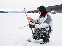 Zachary Adamczyk loads up a tip up with bait Friday morning in Meredith Bay in preparation for the Great Meredith Rotary Ice Fishing Derby.  (Karen Bobotas/for the Laconia Daily Sun)