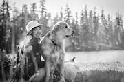 Woman and her dog (golden retriever) sitting on the shore of Bull Run Lake, Carson-Iceberg Wilderness, Stanislaus National Forest, California