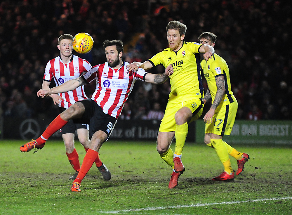 Lincoln City's Ollie Palmer vies for possession with Cheltenham Town's Jamie Grimes<br /> <br /> Photographer Andrew Vaughan/CameraSport<br /> <br /> The EFL Sky Bet League Two - Cambridge United v Lincoln City - Friday 9th February 2018 - Abbey Stadium - Cambridge<br /> <br /> World Copyright © 2018 CameraSport. All rights reserved. 43 Linden Ave. Countesthorpe. Leicester. England. LE8 5PG - Tel: +44 (0) 116 277 4147 - admin@camerasport.com - www.camerasport.com