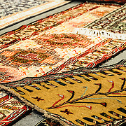 A mix of Turkish carpet designs on display in a store at the Arastar Bazaar, a small bazaar next to the Sultanahment Camii (Blue Mosque) in Istanbul, Turkey.
