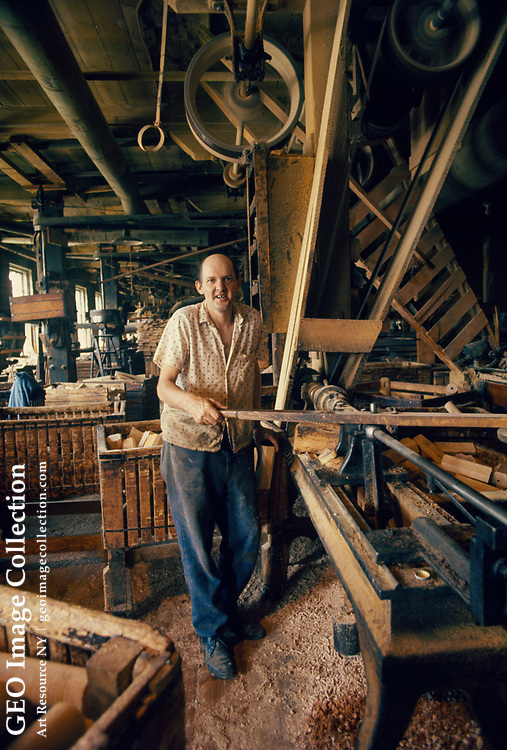 Woodworker uses 19th century old tools on a belt pulley system to turn wood at Vermont Spool and Bobbin factory. The industrial wood spools produced are used in textile industry but now obsolete.