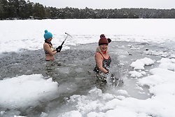 Aviemore, Scotland, UK. 4 February 2021. Loch Vaa is completely frozen and offers opportunity to walk across it. A small boathouse is now icebound and three ladies from the InVaa Dookers wild swimming group use axes to break the ice to allow them to soak in the icy water for a few minutes. Pic; Carolyn Stead and Wendy Cathcart break the ice in Loch Vaa.  Iain Masterton/Alamy Live News