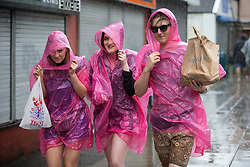 © Licensed to London News Pictures . 11/06/2016 . Manchester , UK . Three women dressed in pink waterproof ponchos arrive at the festival in a heavy downpour . Parklife music festival at Heaton Park in Manchester . Photo credit : Joel Goodman/LNP