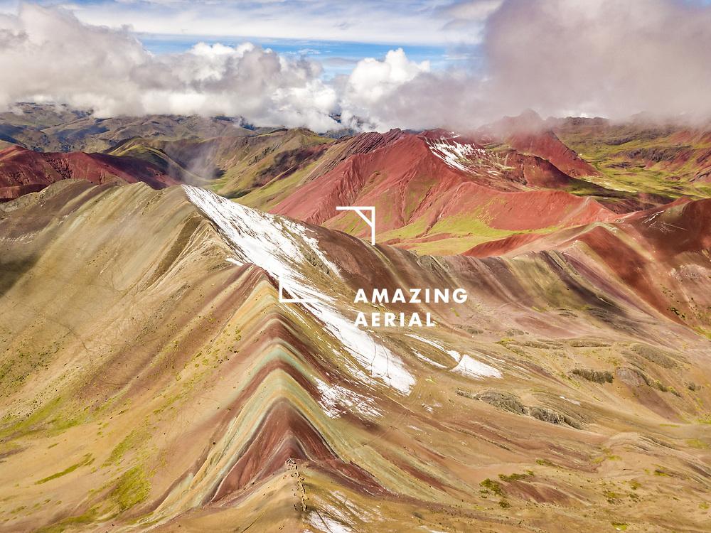 Aerial view of peaks of Vinicunca in clouds, Rainbow Mountain, Peru.