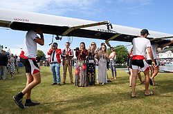 © Licensed to London News Pictures. 04/07/2018. Henley-on-Thames, UK. A group of friends watch as a rowing team takes rot the water on day one of the Henley Royal Regatta, set on the River Thames by the town of Henley-on-Thames in England. Established in 1839, the five day international rowing event, raced over a course of 2,112 meters (1 mile 550 yards), is considered an important part of the English social season. Photo credit: Ben Cawthra/LNP