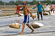Man carries farmed salt in traditional shoulder baskets, Bangkok, Thailand
